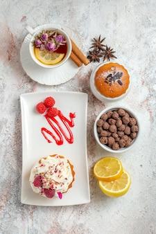 Vista dall'alto di una deliziosa torta cremosa con una tazza di tè e fette di limone su bianco