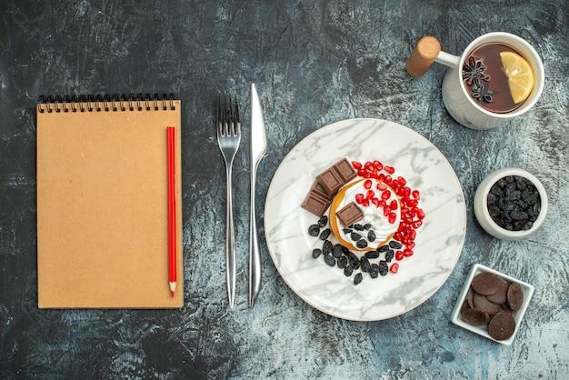 Torta cremosa gustosa vista dall'alto con una tazza di tè su sfondo chiaro-scuro