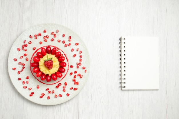 Vista dall'alto gustosa torta cremosa con cornioli sulla scrivania bianca chiara