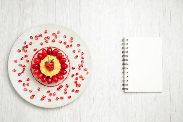Вкусный сливочный торт с кизилом на белом столе, вид сверху