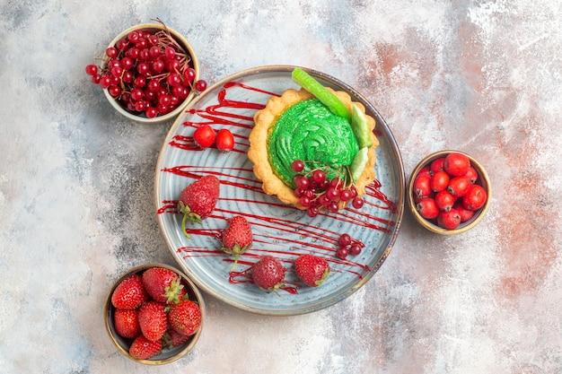 Vista dall'alto gustosissima torta cremosa con frutta fresca su dolce torta da dessert biscotto pavimento chiaro