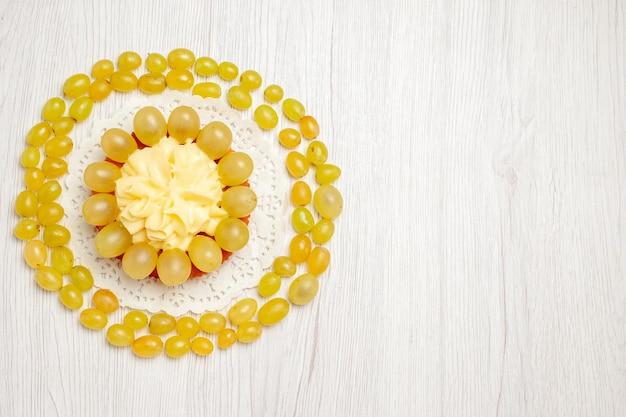 Vista dall'alto una gustosa torta cremosa con uva verde fresca su un biscotto biscotto con crema alla frutta da scrivania bianca chiara