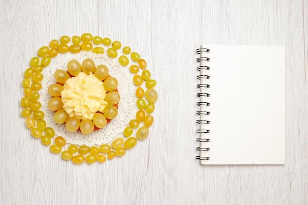 Vista dall'alto gustosissima torta cremosa con uva verde fresca su scrivania bianca chiara torta alla crema di frutta biscotti biscotti