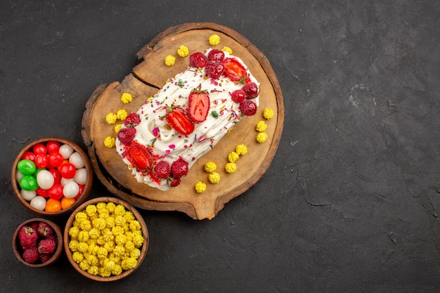Top view of yummy creamy cake with fruits and candies on black