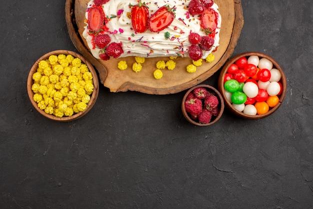 Vista dall'alto di una deliziosa torta cremosa con frutta e caramelle su nero