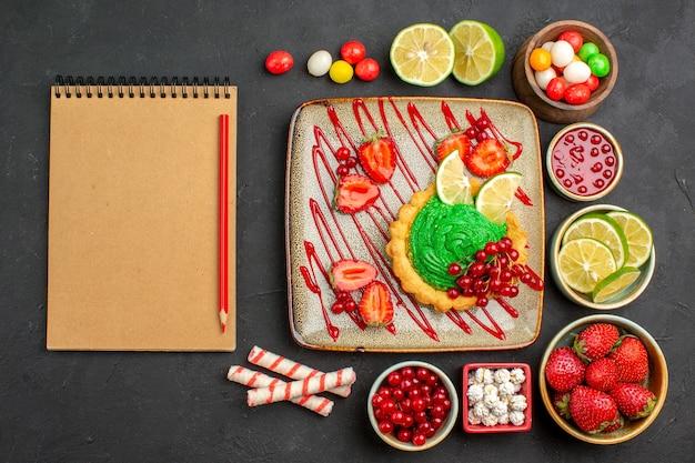 Vista dall'alto gustosa torta cremosa con frutta su sfondo scuro biscotto dolce colore dolce