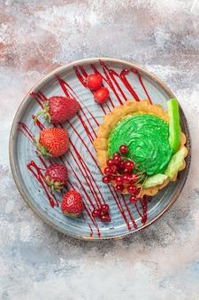 Torta cremosa gustosa vista dall'alto con frutta sul tavolo luminoso, torta dolce dessert biscotto