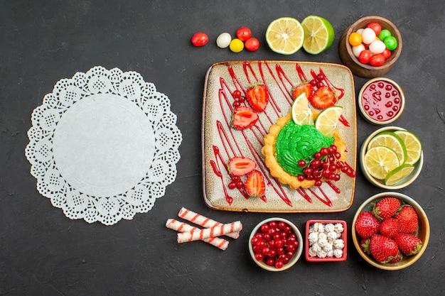Вид сверху вкусный сливочный торт с фруктами на темном фоне бисквитный десерт сладкого цвета