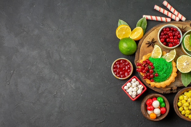 Вид сверху вкусный сливочный торт с фруктами на темном фоне место без сладкого печенья