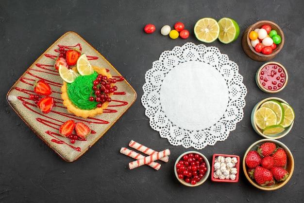 灰色の背景にフルーツとおいしいクリーミーなケーキの上面図デザートカラービスケット甘い
