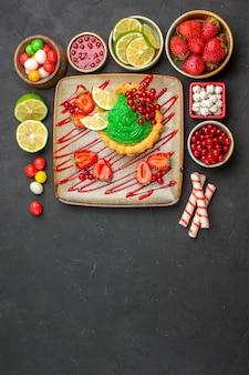 暗い背景にフルーツとおいしいクリーミーなケーキの上面図ビスケットデザート甘い