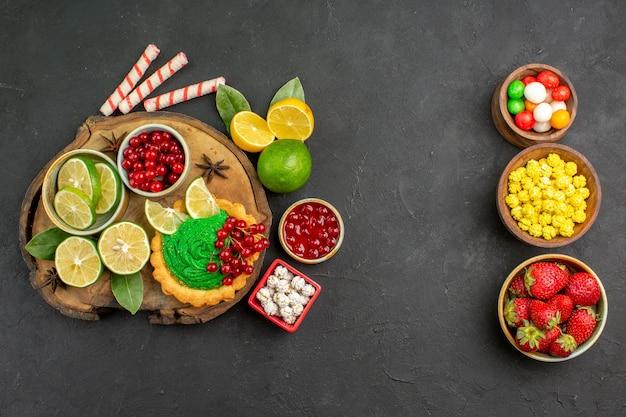 暗い背景の甘いクッキービスケットにフルーツとおいしいクリーミーなケーキの上面図