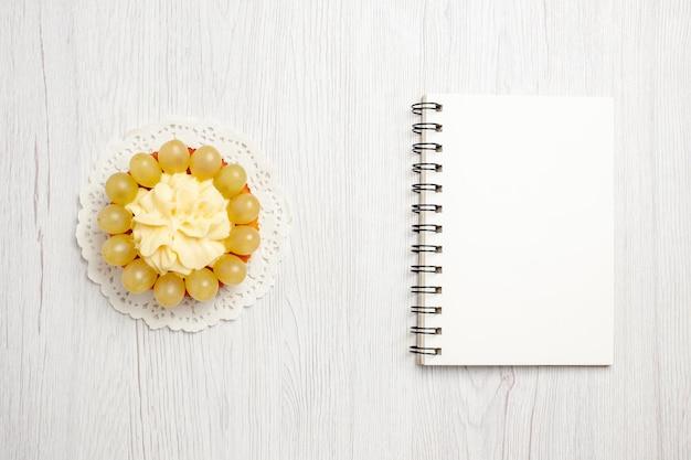 上面図白い机の上の緑のブドウとおいしいクリーミーなケーキフルーツクリームケーキビスケットクッキー