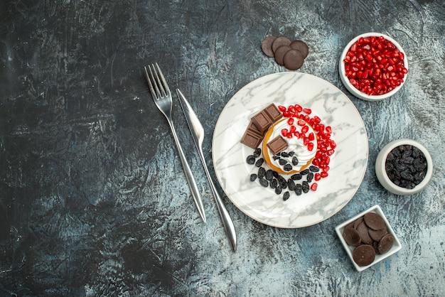 Вид сверху вкусный сливочный торт с изюмом и чашкой чая на светло-темном фоне