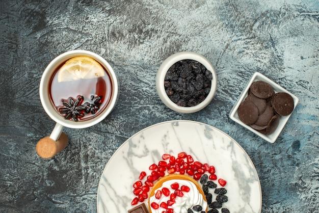 Vista dall'alto gustosa torta cremosa con uvetta e tazza di tè su sfondo chiaro-scuro