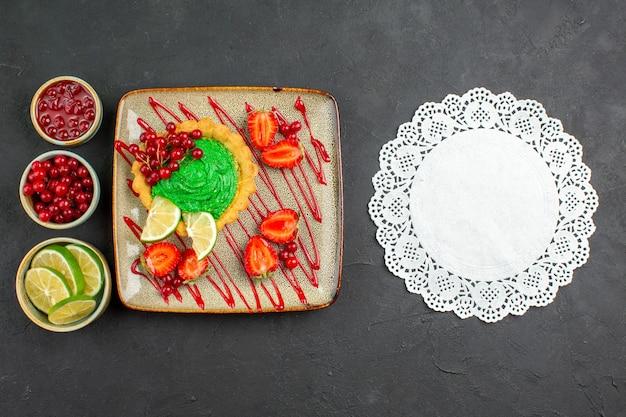 暗い背景の甘いお茶の砂糖デザートにイチゴとおいしいクリーミーなケーキの上面図