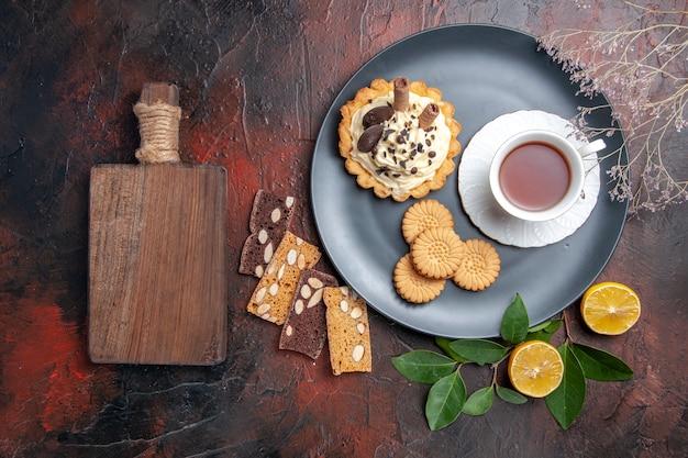 Вид сверху вкусный сливочный торт с чаем и печеньем на темном столе сладкий торт десерт