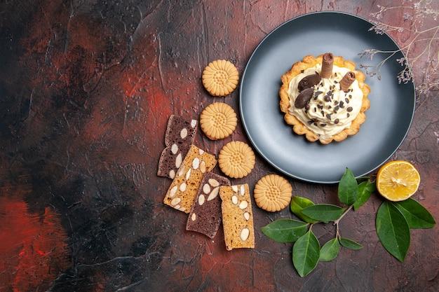 暗いテーブルの上のクッキーとおいしいクリーミーなケーキの上面図甘いケーキのデザート