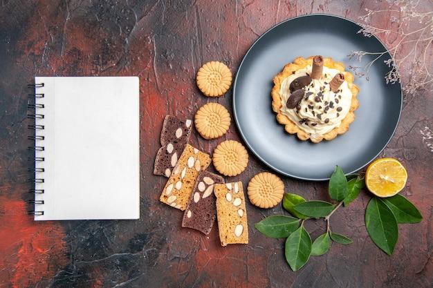 暗い床の甘いケーキのデザートにクッキーとおいしいクリーミーなケーキの上面図
