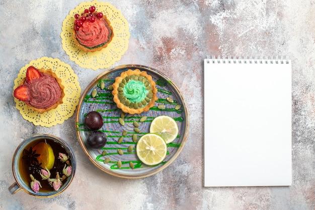トップビュー明るい背景の甘いキャンディビスケット砂糖にお茶とおいしいクリーミーなケーキ