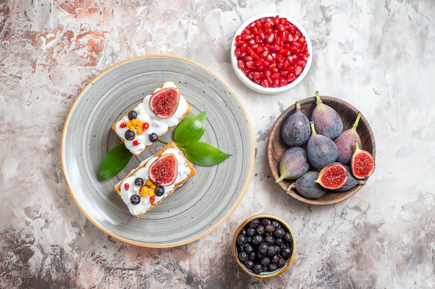 Top view yummy creamy cakes with fresh fruits on light background
