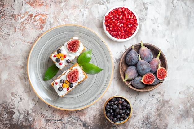 Вид сверху вкусные сливочные пирожные со свежими фруктами на светлом фоне