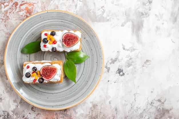 明るい背景に新鮮な果物とおいしいクリーミーなケーキの上面図