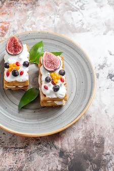 밝은 배경에 신선한 과일과 함께 상위 뷰 맛있는 크림 케이크