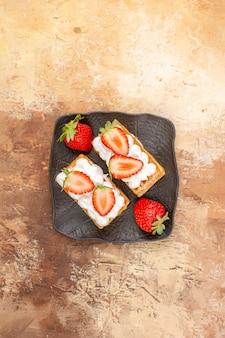 明るい背景にフルーツとおいしいクリーミーなケーキの上面図