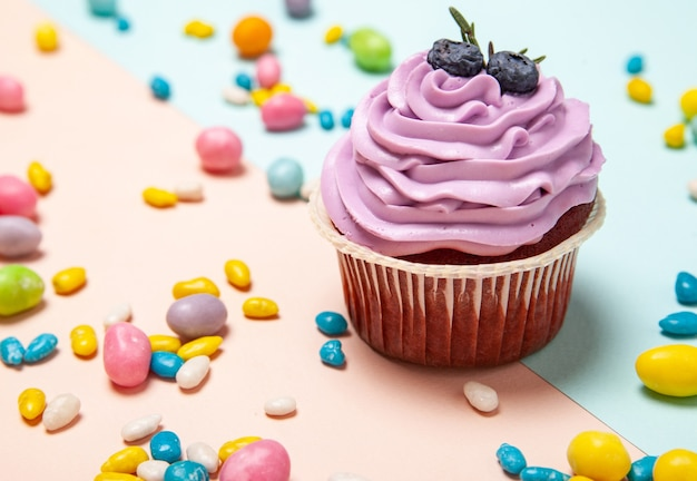 Top view of yummy cupcake with cream and blueberries placed amidst colorful sweets on peach and blue background