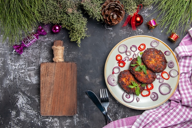 Top view yummy cutlets with onion rings on light-grey background meat dish photo