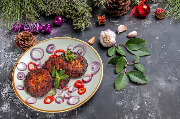 灰色の背景にオニオンリングが付いたおいしいカツレツの上面図食事写真皿肉