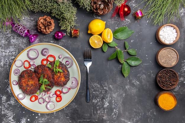 Вид сверху вкусные котлеты с луковыми кольцами на сером столе, блюдо, мясная кухня