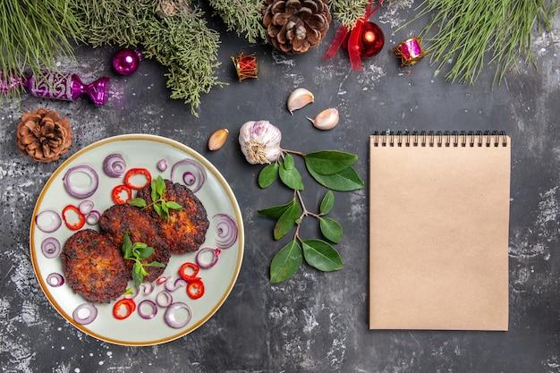 灰色の机の食事の写真の皿の肉にオニオンリングが付いている上面図おいしいカツレツ