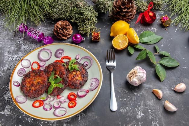 Вид сверху вкусные котлеты с луковыми кольцами на сером полу блюдо мясная кухня