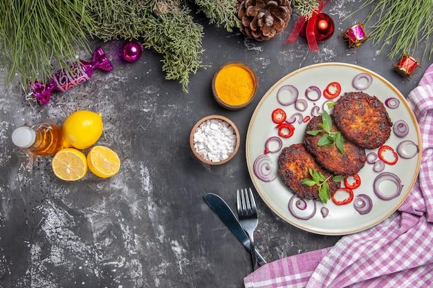 ライトグレーの背景にオニオンリングが付いたおいしいカツレツの上面図食事写真肉料理