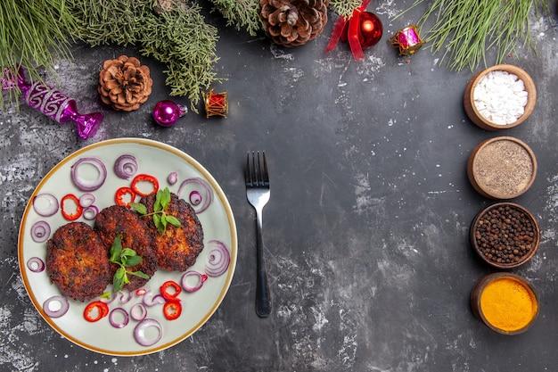 灰色の背景にオニオンリングが付いたおいしいカツレツの上面図肉骨粉料理