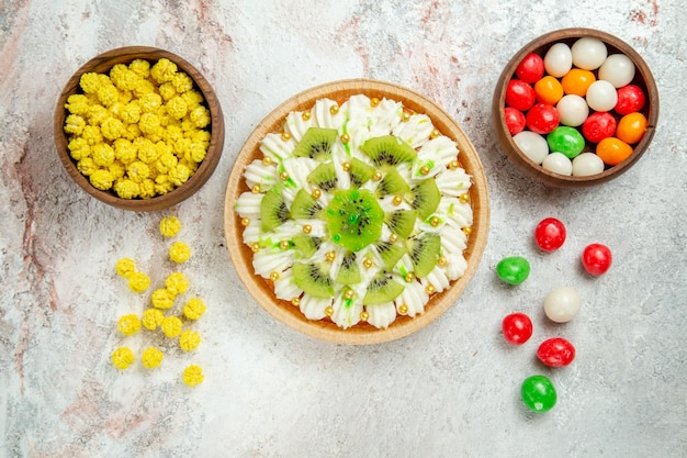 Top view of yummy dessert consists of white cream and sliced kiwis with candies on white table