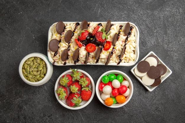 Vista dall'alto squisito dessert con biscotti e caramelle su sfondo scuro biscotto alle noci biscotti alla frutta dolce zucchero