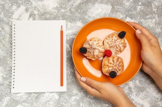 白い背景の上の砂糖粉とメモ帳でおいしい生地ケーキの上面図