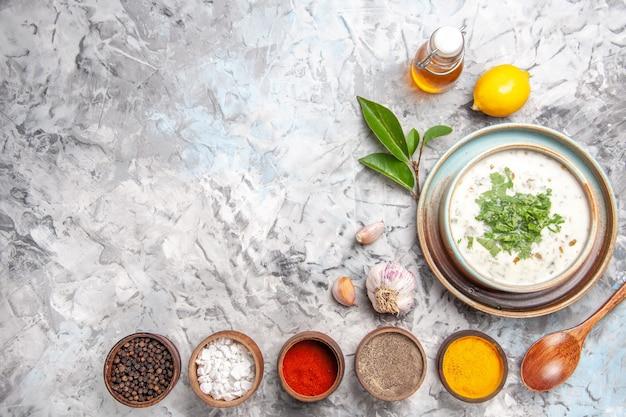 하얀 접시 우유 수프에 조미료를 곁들인 맛있는 도브가 요구르트 수프