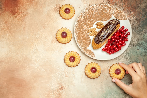 Top view yummy eclair with red berries and cookies on the light table cake dessert sweet