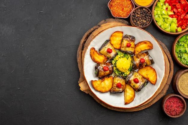 Vista dall'alto involtini di melanzane gustosi piatti cucinati con patate e condimenti sulla superficie scura pasto per piatti cena cibo