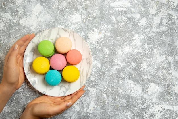 Вид сверху вкусные французские макароны, красочные пирожные внутри тарелки на белой поверхности