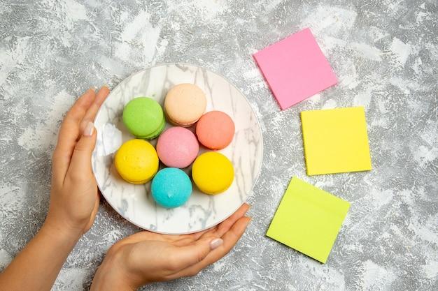Vista dall'alto deliziose torte colorate di macarons francesi all'interno del piatto su superficie bianca