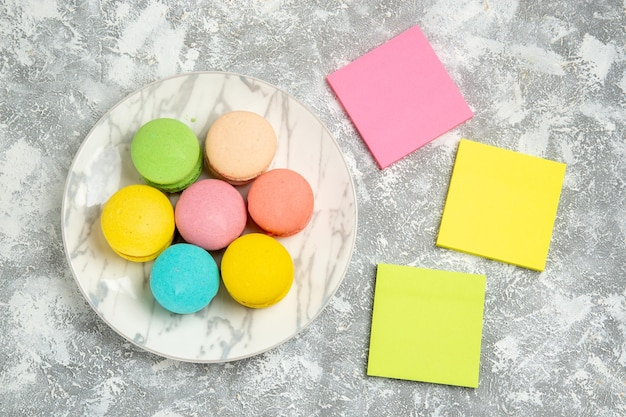 Top view yummy french macarons colorful cakes inside plate on white surface