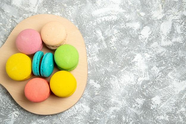 Вид сверху вкусные французские макароны, красочные торты на белом столе