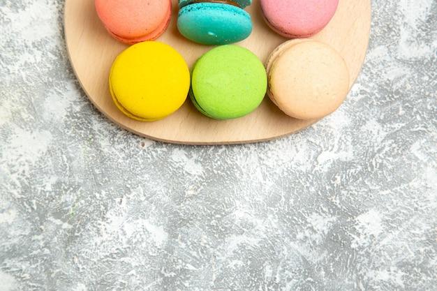 Vista dall'alto deliziose torte colorate di macarons francesi su superficie bianca