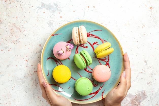 Вид сверху вкусные французские макароны внутри тарелки на белом пироге, бисквитном сладком