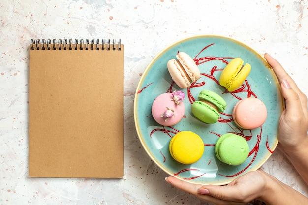 Вид сверху вкусные французские макароны внутри тарелки на белом пироге, печенье, сладостях